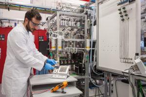 Promovendus Georgios Zafeiropoulos met fotoelektrochemische cel in het DIFFER artificial leaf laboratorium - foto: DIFFER / Bram Lamers